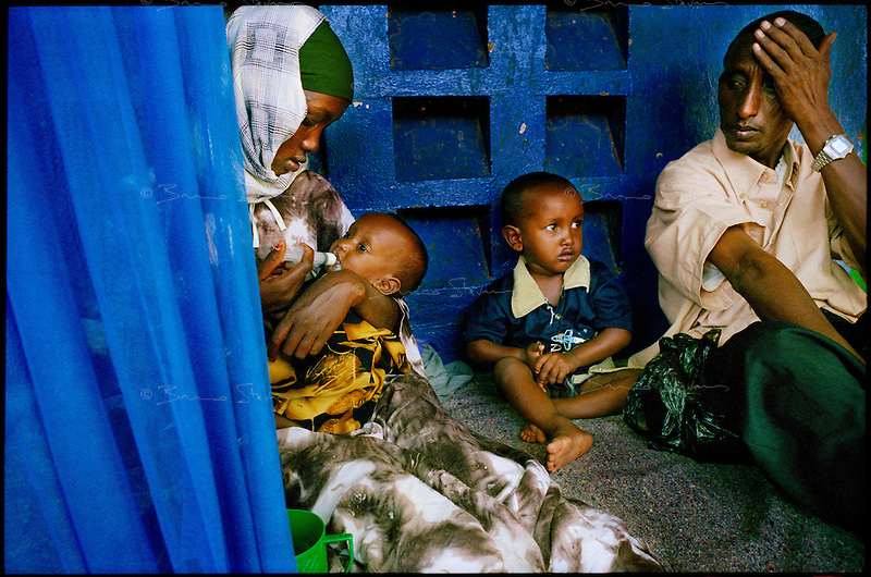 Mandera, NE Kenya, March 2006.Mandera district hospital, ACF operated TFC. Faduma Sheikh Hassan, 19, left, feeds her daughter Sumaya Yusuf, 9 months with enriched milk, with her son Abdel Kader Yusuf, 2 and her husband Yusuf Ali, 32, right. Millions semi-nomadic herdsmen who are leaving the bush to come and live in camps near villages as their livestock is decimated by a persistent drought, abandonning their traditional lifestyle.