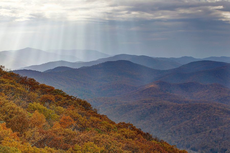 Streams on sunlight filter thru the clouds covering the fall colored Blue Ridge Mountains in Nelson County, Va. Photo/Andrew Shurtleff