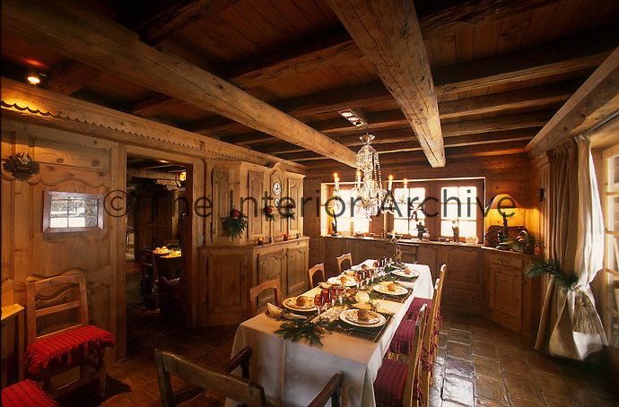 The generously proportioned panelled dining room has a tiled floor and a low beamed ceiling
