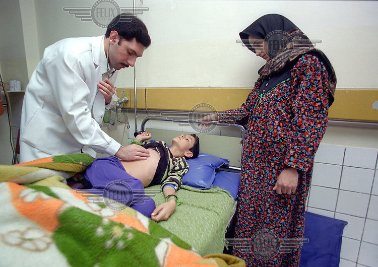 "(February 1998) Nine year old Haiman Sabri being examined by a pediatrician , doctor Yaser Raouf, with his mother bedside at the Saddam hospital in Baghdad. <br /> According to his doctor Haiman had a curable infection, but due to lack of anti biotics suffered life threatening complications.  <br /> Due to UN sanctions the hospital was lacking many medicines, and the civilians suffered due to lack of food as well. <br />  Former U.N. Humanitarian Coordinator in Iraq Denis Halliday estimated the resulting deaths : ""Two hundred thirty-nine thousand children 5 years old and under"" as of 1998.<br /> <br /> The sanctions against Iraq were a near-total financial and trade embargo imposed by the United Nations Security Council on the Iraqi Republic.<br /> <br /> <br /> ©Fredrik Naumann/Felix Features"