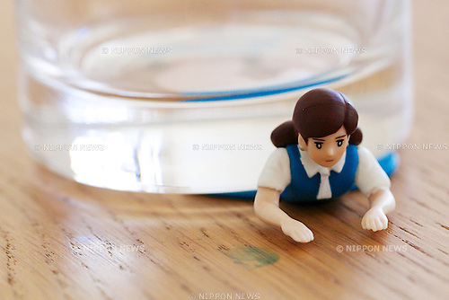 "A figure of ""Cup no Sococo"" squashed under a glass on August 19, 2014 in Tokyo, Japan. These mini figures are popular amongst young Japanese women who often use them when composing pictures of their lunch. The name Cup no Fuchiko translates to  or ""office lady, or OL, on the side of a cup"" and the figures are sold as drink ornaments. Made by  Kitan Club CO. LTD Cup no Fuchiko was created by the manga artist Katsuki Tanaka. There are currently 21 models of Cup no Fuchiko and Kitan Club has also made capsule toys from famous characters such as Street Fighter II, Moomin, Hello Kitty. (Photo by Rodrigo Reyes Marin/AFLO)"