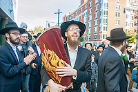 Rabbi Yossel Gansbourg of the Chabad of Harlem celebrates the completion of their Sefer Torah in a Torah parade (Hachnasat Sefer Torah) through the streets of Harlem in New York on Sunday, October 27, 2013. The ten year old synagogue commissioned the hand-written parchment scroll (which contains 304,805 Hebrew letters) two years ago. Harlem was once home to over 200 synagogues before the Great Depression and current census records have shown that the caucasian population now outnumbers african-americans.  (© Richard B. Levine)