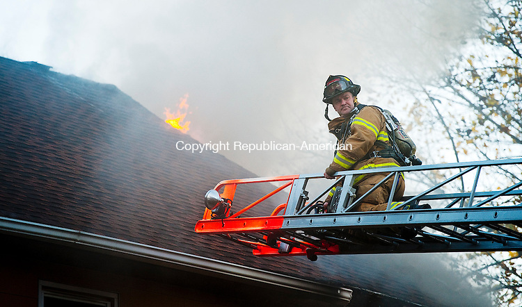 WATERBURY, CT--- -112015JS01--A firefighter waits for a ladder to be brought up after Waterbury firefighters were called out on Friday to battle a house fire at 46  St. Jean Street in Waterbury. <br />  Jim Shannon Republican-American