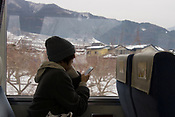 A passenger on the train to Yudanaka, as the train approaches the township.