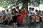 Bellerby Feast,  Bellerby Yorkshire UK.Local children around the village tree have a snack before the mid day fancy dress competition. Which I judged.