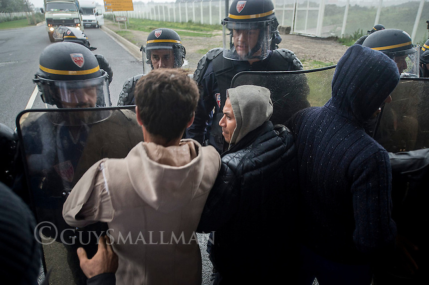 A stand off ensues between refugees and migrants from the Calais 'Jungle' camp and CRS riot police who were preventing residents from leaving the main entrance during a visit to Calais by a senior member of the French government.