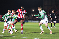 Lincoln City's John Akinde shields the ball from Yeovil Town's Alex Pattison, left, and Tom James.<br /> <br /> Photographer Andrew Vaughan/CameraSport<br /> <br /> The EFL Sky Bet League Two - Lincoln City v Yeovil Town - Friday 8th March 2019 - Sincil Bank - Lincoln<br /> <br /> World Copyright © 2019 CameraSport. All rights reserved. 43 Linden Ave. Countesthorpe. Leicester. England. LE8 5PG - Tel: +44 (0) 116 277 4147 - admin@camerasport.com - www.camerasport.com