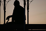 A cable car grip man was silhouette by the sunset on Hyde Street hill in San Francisco, California.