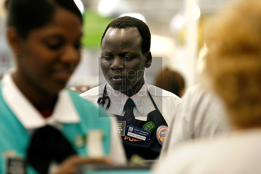 "John Madut (cq) works at the Toco Hills Publix on Friday, Sept. 1, 2006. One of the ""Lost Boys of Sudan,"" Madut has worked at the grocery store since 2003. This year he returned to Sudan for the first time since leaving and saw that his home town is in desperate need of clean drinking water. He's trying to help by raising funds for a new well, but has found the effort to be a financially monumental task."