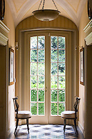 French doors at the end of a vaulted corridor lead into the garden