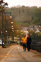 "Pictured: A couple stroll during an unusually dark morning by the seaside village of Mumbles near Swansea, UK. Monday 16 October 2017<br /> Re: Remnants of Hurricane Ophelia are expected to bring strong gusts of wind to Wales when it hits Britain's shores.<br /> The hurricane, making its way from the Azores in the Atlantic Ocean, will have weakened to a storm when it arrives.<br /> A Met Office amber ""be prepared"" warning has been issued in some areas bringing ""potential danger to life""."