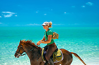 Horse rider troting on beach. Providenciales. Turks and Caicos.