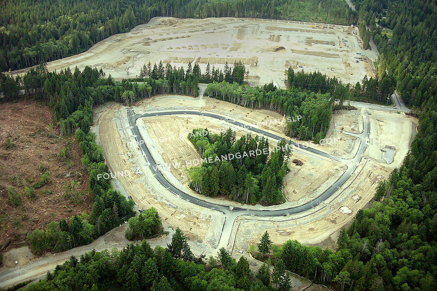 an aerial view showing an evergreen forest cleared in a curved swath with new roads in place through bare dirt, heavy equipment parked at the far edge, and a swath of slashed land awaiting a new road.