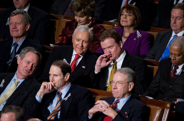 UNITED STATES - JANUARY 25:  Sen. Orrin Hatch, R-Utah, red tie, has a word with Sen. Jim Webb, D-Va., in the House Chamber during President Barack Obama's State of the Union address.  Many Senators and Representatives from opposite sides of the aisle choose to sit with each other to help alleviate partisanship.  (Photo By Tom Williams/Roll Call)