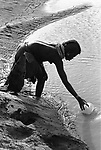 A Turkana  woman collects water from a  borehole  and then  has to carry the load  back to her village over 1 km  away.