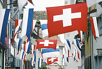 Switzerland. Zoug. Old town. The first of august is the swiss national day. Swiss and zoug (blue and white) flags in the street of the old town. © 1989 Didier Ruef