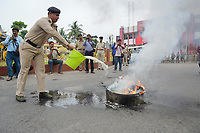 Pictured: A police officer douses a burning tyre with water. Re: Activists of the Congress political party clash with police in protest against price rises in oil, gas and other daily commmodities by BJP government in Agartala, in the Tripura area of India. Monday 10 September 2018