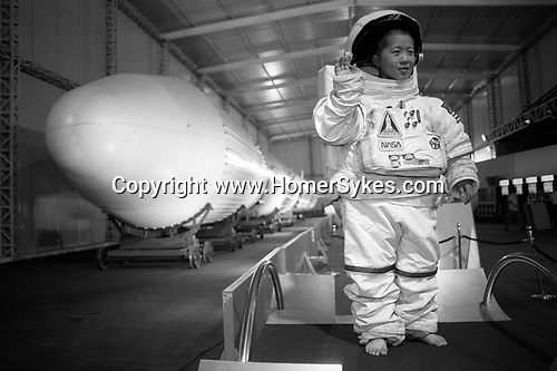 "A small boy wearing an oversize NASA space suit while being photographed besides the Chinese ""Long March Number 3"" rocket, at the Zhongshan Park rocket exhibition. Shanghai, the Peoples Republic of China. 2000"