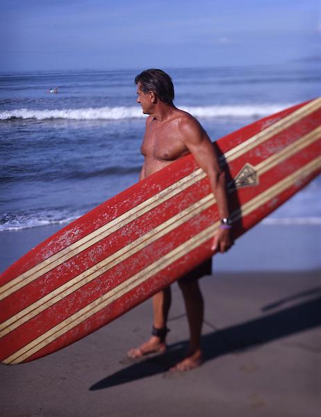 Surfer Gio Giovennella, 63, on a beach near Lahaina, Maui. Photo by Kevin J. Miyazaki/Redux