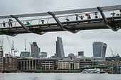 Tourists with umbrellas on the Thames Millenium Bridge London in heavy rain.