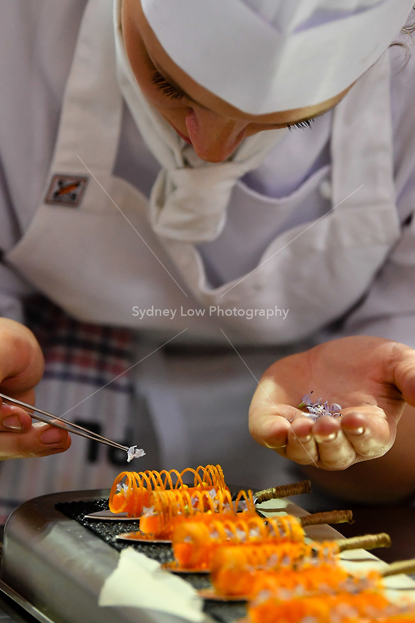 Melbourne, 30 May 2017 - Laura Skvor commis chef assisting Michael Cole of the Georgie Bass Cafe & Cookery in Flinders prepares a garnish for the meat platter at the Australian selection trials of the Bocuse d'Or culinary competition held during the Food Service Australia show at the Royal Exhibition Building in Melbourne, Australia. Photo Sydney Low