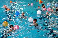 Kinderen watertrappelen met ballonnen voor hun zwemdiploma