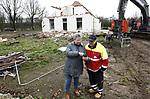 """Foto: VidiPhoto<br /> <br /> DIDAM – Het echtpaar Snelting-de Reus uit Didam loopt vrijdag nog een laatste keer door en om hun oude huis langs de A12 bij Didam dat op dit moment gesloopt wordt. Het echtpaar heeft er ruim 40 jaar gewoond. Van de altijd keurig onderhouden woning en tuin is weinig meer over. Ze delen hun emoties samen met de slopers van de Rouwmaat Groep uit Groenlo, die de opdracht hebben van Rijkswaterstaat om het pand te ontmantelen. Jan Snelting herinnert zich dat automobilisten op de A12 met pech bij hen vaak een sleutelset kwamen halen. """"Die kreeg ik nooit terug."""" De sloop van woningen en gebouwen voor de verbreding van de A12 is deze week begonnen. Op de plek van de Sneltings krijgt de A12 een nieuwe oprit. Tussen Westervoort en knooppunt Oud-Dijk komen bovendien twee extra rijstroken. Op die plek staan dagelijks lange files."""