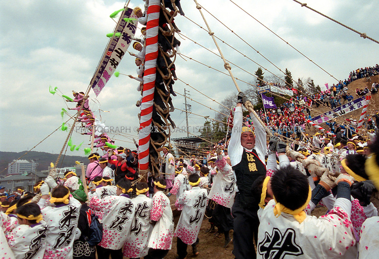 "4/2/2004--Suwa, Japan..Members of a log team try to keep their log balanced as they come down the hill during the Onbashira Festval in Suwa, Japan...The basic purpose of the 1200 year old Onbashira Festival is rooted in Shinto, the indigenous religion of Japan. In the Shinto way of thinking, the Gods, or kami, are living in the natural environment which surrounds human beings. The Onbashira Festival serves as a reminder of the importance of nature to human beings: large fir trees (symbolic ""gods"") are brought down from the mountains, carried into town and set to stand at the outskirts of the Suwa Grand Shrine. In this way, the people of the Suwa region never completely lose their contact with nature and the gods, and they renew this contact at least once every 6 years through Onbashira Festival..Photograph by Stuart Isett.©2004 Stuart Isett. All rights reserved"