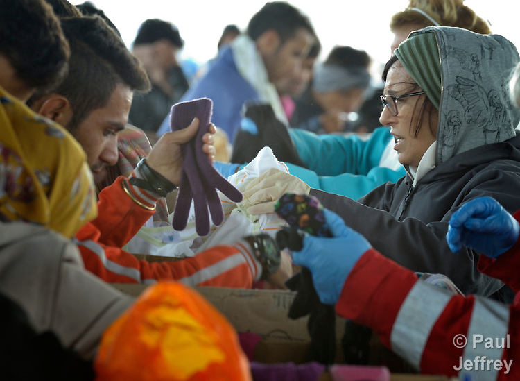 Refugees sort through donated clothing at the border crossing into Austria near the Hungarian town of Hegyeshalom. Hundreds of thousands of refugees and migrants flowed through Hungary in 2015, on their way to western Europe from Syria, Iraq and other countries. The ACT Alliance has provided food and other critical support for refugee and migrant families here and in other places along their journey.