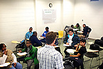 Greg Wahl, left, associate professor at Montgomery College, answers questions from students in his Basic Writing II class, as they brainstormed ideas for their final project. If students pass this class, it allows them to progress to the college level english program. Otherwise students will face the decision to take the remedial class again or drop out.
