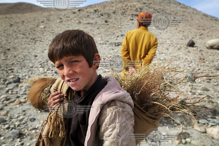 A boy carries a bag of straw near the town of Memlah.