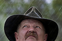 Portrait of Shady Lagoon cattle station manager John Gostilow as he raises looks up into the rain.  <br />  John told me absolutely NOTHIN was going on.  He was the only one out on the station and all the hands had left and all the cows had been moved to higher ground.  I went out anyway... it started to rain.