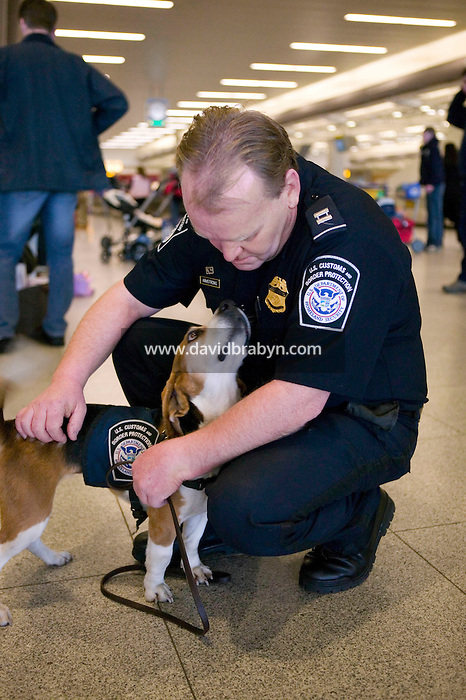 11 April 2006 - New York City, NY - 3 year-old Beagle Alexandra, aka Alex, gets a pat from her handler, officer Jim Amstrong of the K9 unit of the Agricultural division of the Custom and Border Protection agency, after searching through passengers' luggage for illegally imported food at the JFK airport in New York City, US, 11 April 2006.