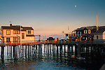 Moonrise at sunset over buildings on Stearns Wharf, Santa Barbara, California