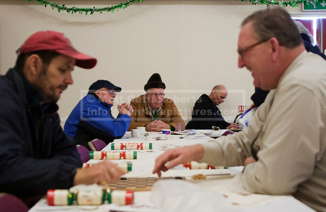 As Christmas dinner cooks in a nearby kitchen, two men play draughts at a Christmas shelter for the vulnerable and homeless in Cheltenham, Gloucestershire.