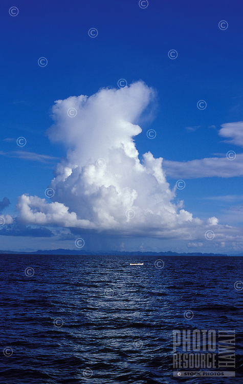 Outrigger fishing canoe under in blue sea under white thunderhead coud, Siargao Island, Philippines