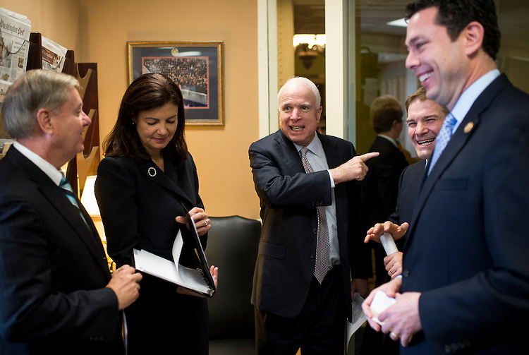UNITED STATES - OCTOBER 30: Sen. John McCain, R-Ariz., center, jokes with Rep. Jim Jordan, R-Ohio, in the Senate Radio/TV Gallery office before their news conference on Benghazi on Wednesday, Oct. 30. 2013. Also pictured are Sen. Lindsey Graham, R-S.C., Sen. Kelly Ayotte, R-N.H., and Rep. Jason Chaffetz, R-Utah. (Photo By Bill Clark/CQ Roll Call)