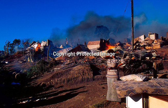 DIENVFI00056.Environment. Fire. An unidentified woman is devastated because of a shack fire that destroyed her home on July 6, 2001, in Duncan Village, a poor township outside East London in Eastern Cape province, South Africa. Eastern Cape is the poorest province in South Africa. Shack fires are very common as the shacks are built very close to each other and people are using paraffin stoves which easily fall over and the fires spread quickly. South Africa is facing a severe backlog of housing for the poor. The ANC government promised to build 1 million houses during the first democratic election in 1994..©Per-Anders Pettersson/iAfrika Photos
