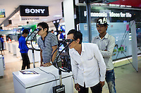 May 27, 2012 - Phnom Penh, Cambodia. People look at a TV through 3-D goggles in one of the biggest malls of Phnom Penh. © Nicolas Axelrod / Ruom