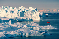 Small fishing boat dwarfed by icebergs in the Icefjord. Ilulissat. Jacobshavn, West Greenland