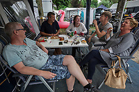 Switzerland. Canton Ticino. Tenero. Camping Campofelice. The family Van der Ham from Netherlands enjoys a good time with a Dutch friend (L) met in the campground. Lucie Van der Ham (R), the wife of Cees (second left) and the mother of Sven (second right) has been coming over the last 40 years every year for one or two holidays in the campsite. Her parents were coming before she was born. Zara (C) is the girlfriend of Sven and both are the third generation spending their holidays in Camping Campofelice. A Giant X-Large Inflatable Flamingo Pool Float for adults and kids is laid on the grass. A campervan (or camper van), sometimes referred to as a camper, or a caravanette, is a self-propelled vehicle that provides both transport and sleeping accommodation. A motorhome (or motor coach is a type of self-propelled recreational vehicle (RV) which offers living accommodation combined with a vehicle engine. Motorhomes are part of the much larger associated group of mobile homes which includes caravans, also known as tourers, and static caravans. A caravan, travel trailer, camper or camper trailer is towed behind a road vehicle to provide a place to sleep which is more comfortable and protected than a tent. It provides the means for people to have their own home on a journey or a vacation. Campers are restricted to designated sites for which fees are payable. 21.07.2018 © 2018 Didier Ruef