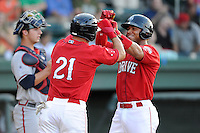 Yoan Moncada (24) of the Greenville Drive, right, is congratulated by Nick Longhi (21) after scoring a run in a game against the Rome Braves on Friday, June 12, 2015, at Fluor Field at the West End in Greenville, South Carolina. (Tom Priddy/Four Seam Images)