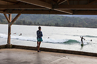 People on Hanalei Pier watch their friends surf in Hanalei Bay, Kaua'i.