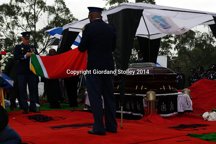 DURBAN - 1 November 2014 - Two officers of the South African Police Services fold the national flag that had been draped over the coffin of slain South African soccer captain Senzo Meyiwa in Durban's Chesterville Cemetery. Meyiwa, who was also the goal keeper for Orlando Pirates, was gunned down in Vosloorus a week earlier. while visiting his girlfriend's house during a robbery. Thousands attended his funeral service earlier in the day. Picture: Allied Picture Press/APP