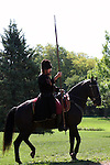 A Russian Cossack riding a horse with a spear