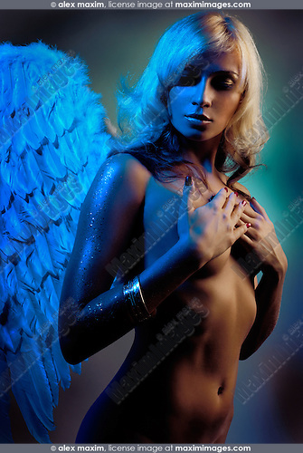 Beautiful naked blond woman with angel wings in blue light artistic photo