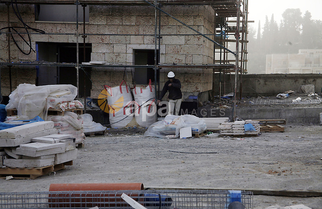"""Labourers work at the construction site of a new housing project at the Jewish settlement of Kiryat Moreh in south Jerusalem on December 20, 2012. Israel has approved plans to build 523 homes in the West Bank, Jewish settlers said, in the first step towards a new settlement """"city"""" that drew furious condemnation from the Palestinians. Photo by Mahfouz Abu Turk"""