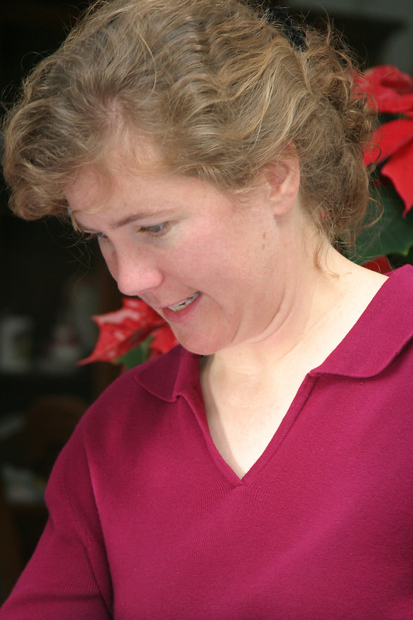 Woman in red shirt gazing down to her right