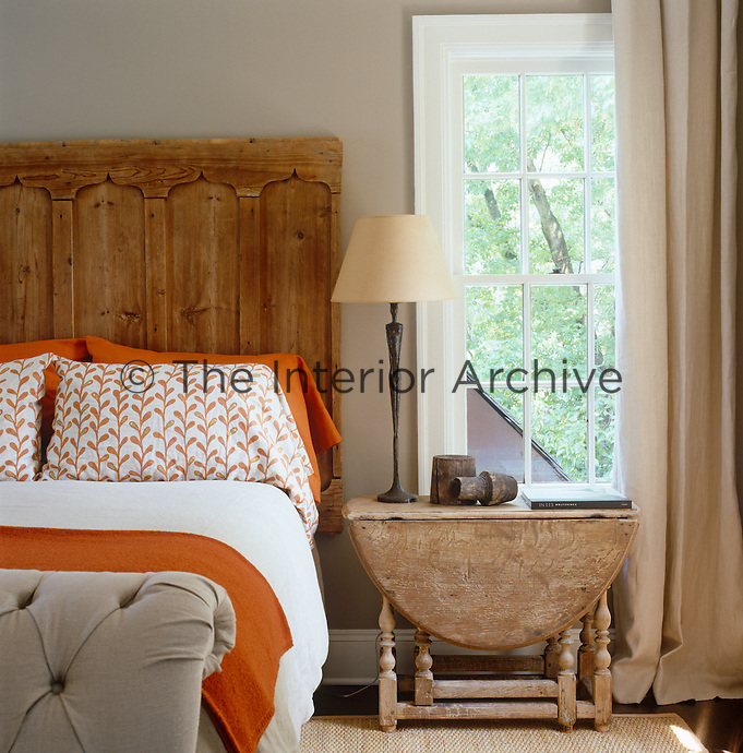 An antique door has been used as a headboard for this bed which has ivy patterned pillow cases matched with orange and white bedding