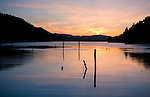 Pilings silhouetted by the setting sun and reflected in the calm water of Wolf Lodge Bay on Lake Coeur d Alene, Idaho.
